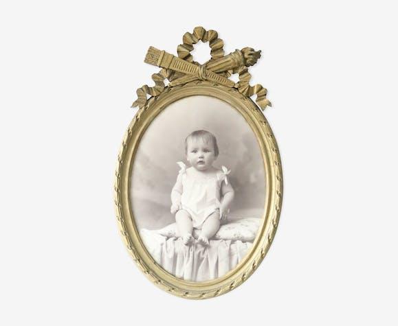 Oval gilded frame, child portrait, old photography