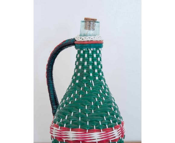 Vintage demijohn wrapped with plastic