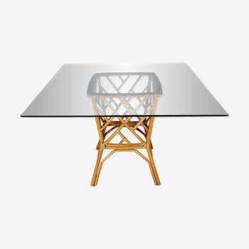 Table de salle à manger en rotin avec un plateau en verre carré
