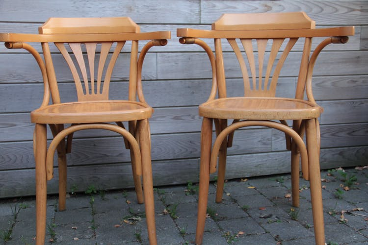 Two chairs with wooden arms turned