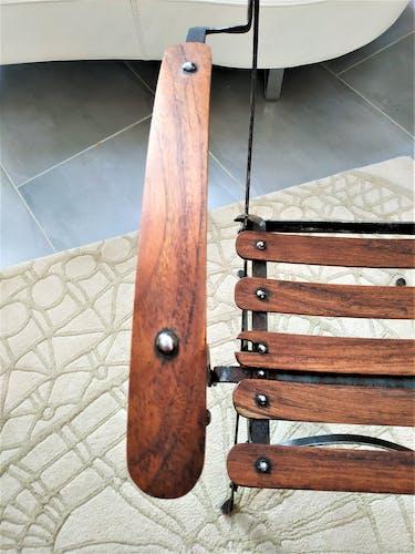 Fauteuil de jardin pliant avec ses lattes de teck sur une structure en fer forgé