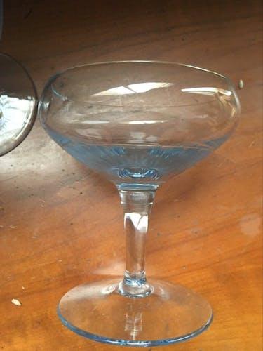 Cinq coupes champagne vintage au verre bleuté.