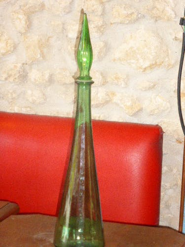 Vintage green faceted glass bottle with its cap 1970