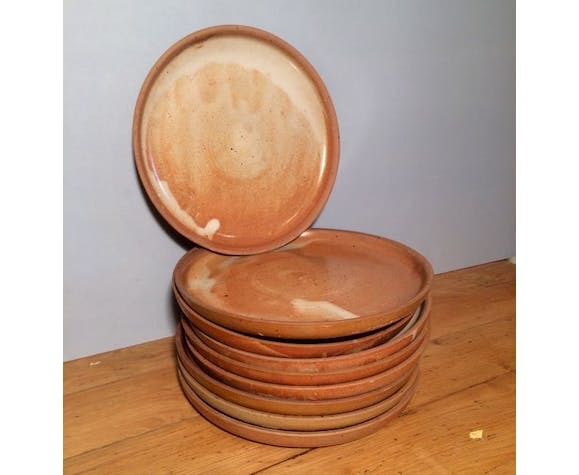 Suite of 9 flat pottery plates of Potter