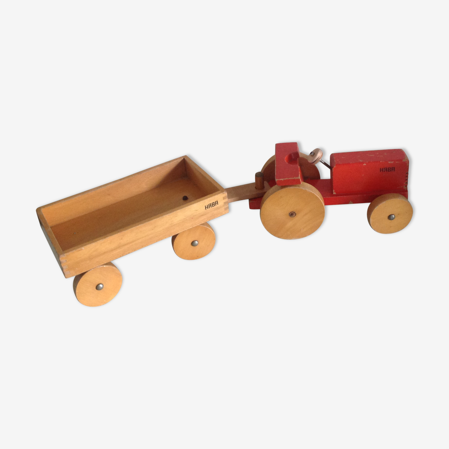 Old wooden red tractor with its trailer Haba