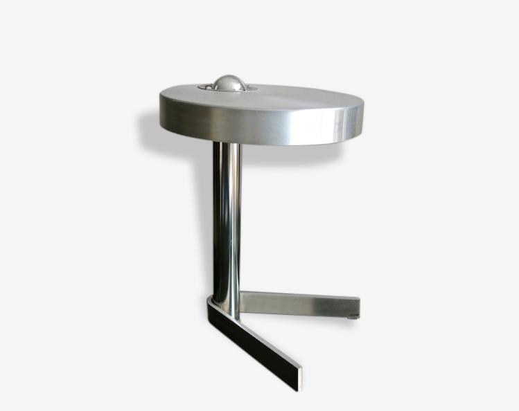 Lampe avec un pied boomerang. Abat-jour en métal avec ampoule apparente.