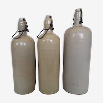 Trio of enamelled sandstone bottles