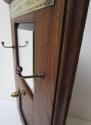 Coat rack with bevelled mirror in oak frame and brass plate