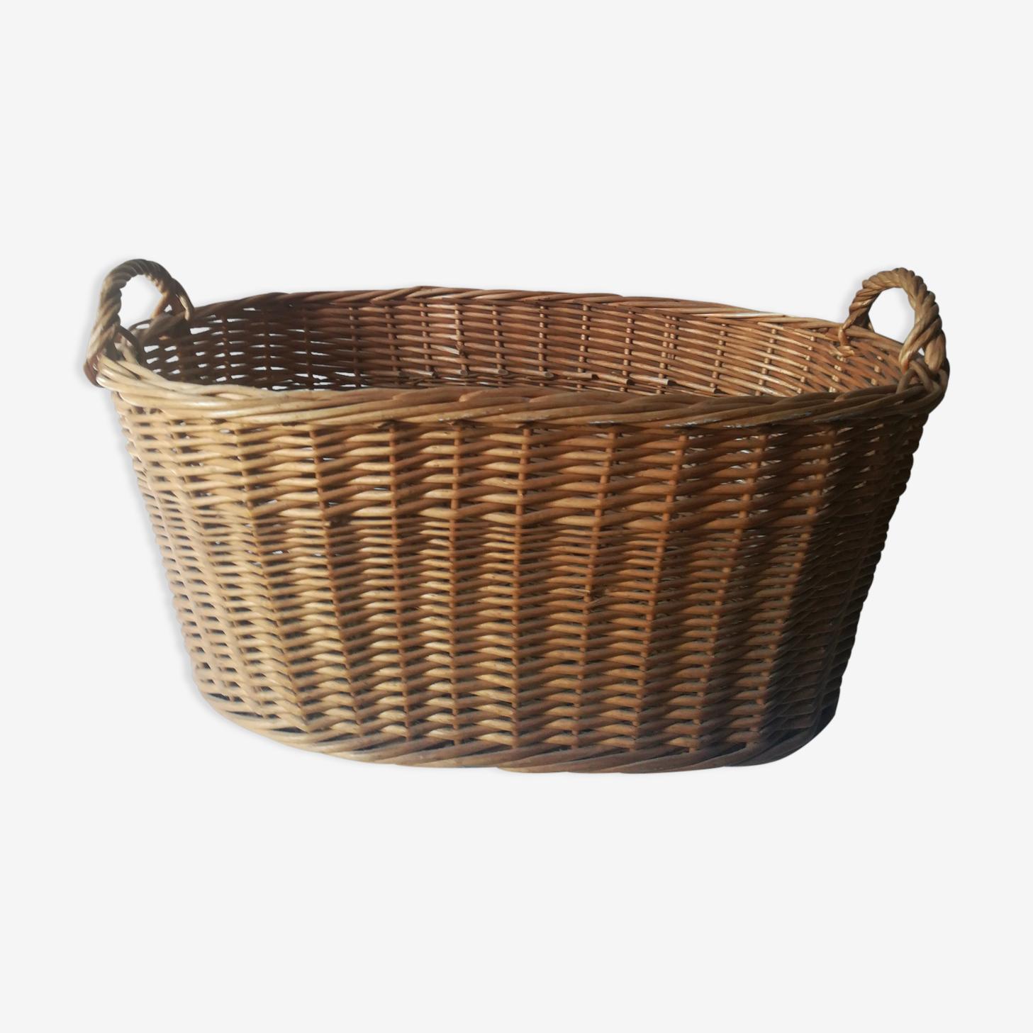 A wicker laundry basket has handles