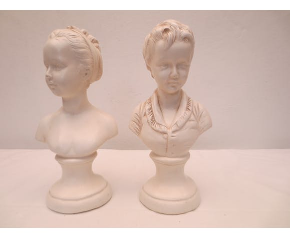 duo of busts of children (girl and boy) in white platter.