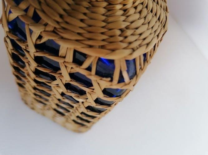 Bouteille bleue couverte d'osier